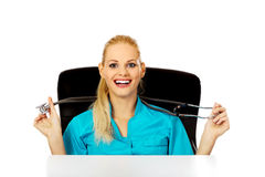 Funny female doctor or nurse sitting behind the desk with stethoscope.  Stock Photo
