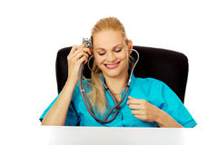 Funny female doctor or nurse sitting behind the desk with stethoscope.  Stock Image
