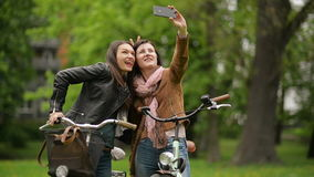 Funny Female Friends Holding Their Bikes are Taking Selfie Using Smartphone. Two Girls are Grimacing While Photographing. Themselves by Mobile Phone in the City stock footage