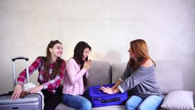 Cute panning trip and preparing carry on luggage on couch in afternoon room. Funny female friends together collect large carry onsuitcases, add up all necessary stock footage