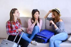 Cute girls going on trip and preparing suitcases on couch in aft. Funny female friends together collect large gray and blue suitcases, add up all necessary Royalty Free Stock Photo
