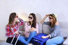 Cute girls going on trip and preparing suitcases on couch in aft. Funny female friends together collect large gray and blue suitcases, add up all necessary Stock Images