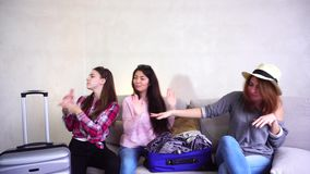 Female girls going on trip and preparing luggage on couch in afternoon room. Funny female friends together collect large gray and blue suitcases, add up all stock video