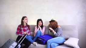 Cool girls going on trip and preparing suitcases on couch in afternoon room. Funny female friends together collect large gray and blue suitcases, add up all stock video