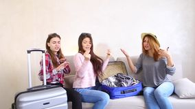 Cute girls going on trip and preparing suitcases on couch in afternoon room. Funny female friends together collect large gray and blue suitcases, add up all stock video footage