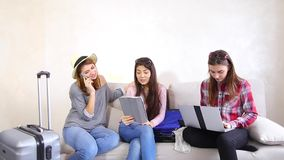 Cute girls going on trip and preparing suitcases on couch in afternoon room. Funny female friends together collect large gray and blue suitcases, add up all stock footage