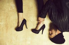 Funny female legs in heels over head of bearded man. Funny female legs in elegant, fashion, stylish, black shoes on high heels over head of bearded man or royalty free stock images