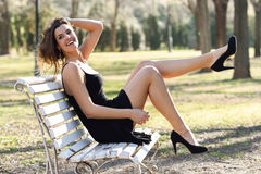 Funny female model of fashion with high heels sitting on a bench Royalty Free Stock Photo