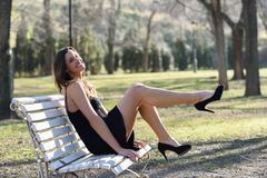 Funny female model of fashion with high heels sitting on a bench Stock Image