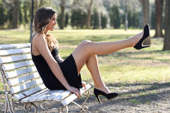 Funny female model of fashion with high heels sitting on a bench. Portrait of funny woman, model of fashion with very long legs, sitting on a bench in an urban Royalty Free Stock Images