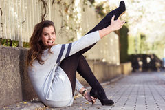 Funny female model of fashion with high heels sitting on the flo Royalty Free Stock Photo