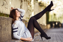 Funny female model of fashion with high heels sitting on the flo Stock Image