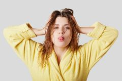 Funny female model makes grimace, shows tongue, has wet hair after taking shower, dressed in yellow bathrobe, glad to have weekend. S, relaxes at home alone Royalty Free Stock Image