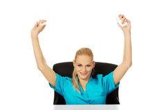 Funny female nurse or doctor sitting behind the desk and holding developed bandage above her head Royalty Free Stock Image