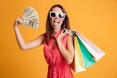 Funny female shopaholic holding fan of money and colorful shoppi Royalty Free Stock Images