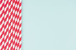 Funny festive bright abstract background - striped red cocktail straws on pastel candy mint color backdrop. Funny festive bright abstract background - striped royalty free stock image