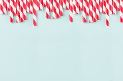 Funny festive bright abstract background - striped red cocktail straws on pastel candy mint color backdrop. Funny festive bright abstract background - striped stock photography
