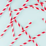 Funny festive bright abstract background - striped red cocktail straws on pastel candy mint color backdrop, pattern, square. Funny festive bright abstract stock photos