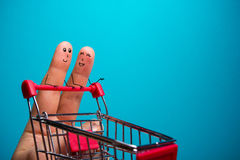 Funny fingers shopping at supermarket with red cart trolley on blue background Stock Image