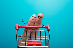 Funny fingers shopping at supermarket with red cart trolley on blue background Royalty Free Stock Photography