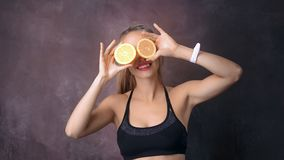 Funny fitness woman posing with half of orange covering eyes playing at black studio background