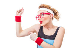 Funny fitness woman pointing on her biceps Royalty Free Stock Photos