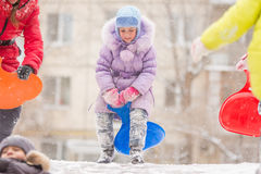 Funny five-year girl runs up to roll down a icy hill. Five-year girl riding winter on a snowy hill surrounded by other children Stock Images