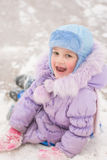 Funny five-year girl sitting rolled down an ice slide Royalty Free Stock Photos