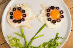 Funny flowers. Fried egg in the shape of fancy flowers, kid food Royalty Free Stock Photography