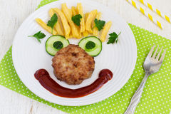 Funny food face with a chop, French fries and cucumber Stock Photo