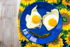 Funny food face smile fried eggs eyes vegetable mouth blue dish. Present food plate - funny food faces smile fried eggs eyes vegetable mouth on blue dish yellow royalty free stock photo