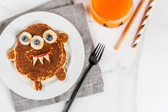 Funny pancakes for Halloween. Funny food for Halloween. Kids breakfast pancake decorated like creepy monster, with banana, berries, with pumpkin smoothie juice Royalty Free Stock Images