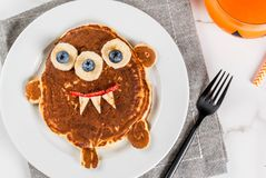 Funny pancakes for Halloween. Funny food for Halloween. Kids breakfast pancake decorated like creepy monster, with banana, berries, with pumpkin smoothie juice Stock Image