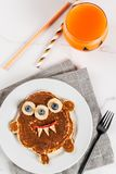 Funny pancakes for Halloween. Funny food for Halloween. Kids breakfast pancake decorated like creepy monster, with banana, berries, with pumpkin smoothie juice Royalty Free Stock Image