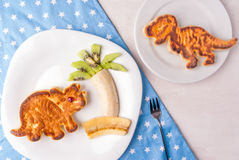 Funny food for kids: Pancake in the form of dinosaurs Stock Image