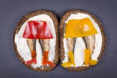 Funny food - sandwich with red and yellow pepper, sprats and soft cheese on the background of black slate , close up Stock Photos