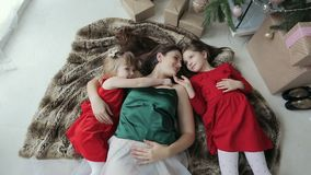 Funny footage of young woman with little daughters lying on the floor looking at each other stock video