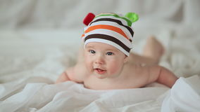 Funny four month old baby lying on his stomach and smiling. Portrait of lying four months old baby girl stock video footage