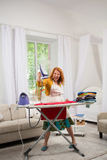 Funny foxy woman dancing with iron. Housewife having fun while ironing clothes Stock Photos