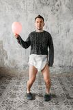 Funny freak man in diaper walks in abandoned house. Grunge room interior stock images