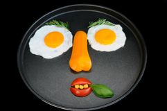 Funny fried eggs face. Funny face from fried eggs and vegetables Stock Photography