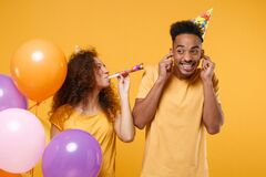 Funny friends couple african american guy girl in birthday hat isolated on yellow background. Holiday party concept