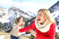 Funny friends joking throwing snowballs stock photo