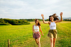 Funny friends jumping in nature. Funny female friends jumping in a green field Stock Images