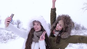 Funny friends are photographed on mobile phone under snow in winter. Season stock footage