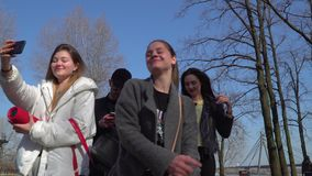 Teenagers shoots themselves on phone during singing and dancing in park. Funny friends sings and dances at the street in park. Teenagers have fun together and stock video