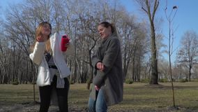 Funny girls dances to the beat of music and singing in the park. Funny friends sings and dances at the street in park. Teenagers have fun together and moving to stock video