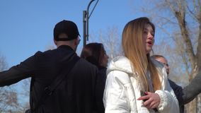 Young girls and guy dancing to the beat of music in park together. Funny friends sings and dances at the street in park. Teenagers have fun together and moving stock footage