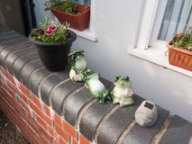 Funny frog statues outside house on front wall stock images