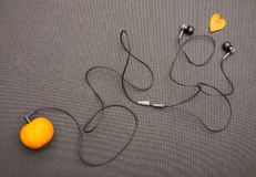 Funny fruity music player: headphones coming from of mandarin on a black background. Royalty Free Stock Photo